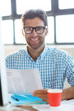 Male business executive holding newspaper and smiling Royalty Free Stock Images