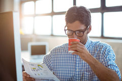 Male business executive reading newspaper while having coffee Stock Photography