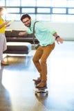 Male business executive riding skateboard Royalty Free Stock Photos