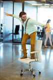 Male business executive standing on chair Royalty Free Stock Photos