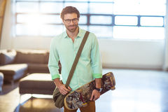 Male business executive standing with skateboard Stock Photos