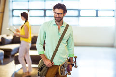 Male business executive standing with skateboard royalty free stock photo