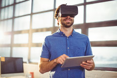 Male business executive in virtual reality headset using digital tablet Stock Photos