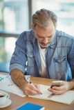 Male business executive writing in organizer while using mobile phone. In office Stock Images