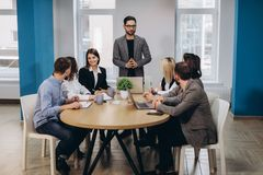 Male business manager meeting with office workers, giving directions in stylish modern office royalty free stock images