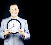 Male business person in gray suit holding a clock Stock Images