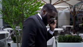 Male in business suit passing by luxury open air cafe talking over cell phone stock image