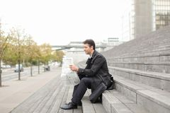 Male business tutor sitting on stairs and reading newspaper. Effect. Tutor dressed in gray coat sitting on rung and read morning newspaper. Articles pleased man Stock Photo