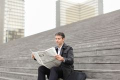 Male business tutor sitting on stairs and reading newspaper. Effect. Tutor dressed in gray coat sitting on rung and read morning newspaper. Articles pleased man Stock Image