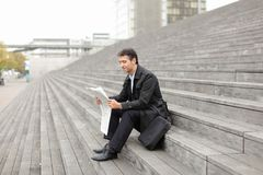 Male business tutor sitting on stairs and reading newspaper. Effect. Tutor dressed in gray coat sitting on rung and read morning newspaper. Articles pleased man Royalty Free Stock Images