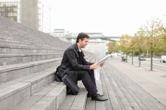 Male business tutor sitting on stairs and reading newspaper. Effect. Tutor dressed in gray coat sitting on rung and read morning newspaper. Articles pleased men Royalty Free Stock Image