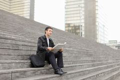 Male business tutor sitting on stairs and reading newspaper. Effect. Tutor dressed in gray coat sitting on rung and read morning newspaper. Articles pleased man Royalty Free Stock Photography