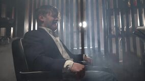 Male businessman in blue jacket and white shirt sits in electric chair and twitches. Torture in gloomy place for young