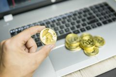 Male businessman hand holding tree titan bitcoin on a background of laptop keyboard and pile of golden coins. Virtual stock photography