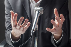 Male businessman having a speech to the public on micro Royalty Free Stock Photo