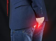 Male businessman holding his ass, hemorrhoids. Black background stock photography