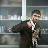 Male businessman holding his cat. And threatens it Stock Photo
