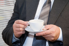 Male businessman relaxing with a cup in hands. Male businessman in the office with a cup of coffee in hands Royalty Free Stock Images