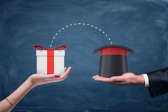 A male businessman`s hand holding a wizards hat and a female hand holding a gift box with connecting dots between. Unexpected bonuses. Gifts and presents stock images