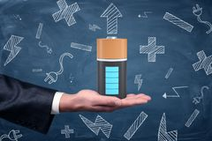 A male businessman`s hand holds up a large fully-charged battery on a blue blackboard background. Power up your business. Energy for success. Rechargeable Stock Photo