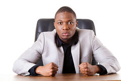 Male businessman sitting in a chair, angry. Royalty Free Stock Photos