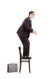 Male businessman standing up on chair ready to jump. Full length portrait of a male businessman standing up on chair ready to jump isolated on white background Royalty Free Stock Images