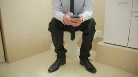 Male businessman watches the news on the phone sitting on the toilet. Businessman watches the news on the phone sitting on the toilet stock video footage