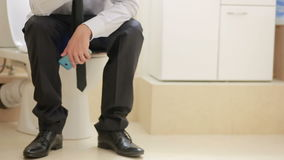 Male businessman watches the news on the phone sitting on the toilet. Businessman watches the news on the phone sitting on the toilet stock footage