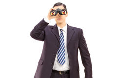 Male businessman watching through binoculars Royalty Free Stock Images