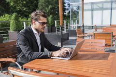 Male businessman or worker in black suit at the table and working on computer. Male businessman or worker with beard and sunglasses in black suit with shirt Royalty Free Stock Photography