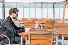Male businessman or worker in black suit at the table and working on computer. Male businessman or worker with beard and sunglasses in black suit with shirt Stock Images