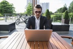 Male businessman or worker in black suit at the table and working on computer. Male businessman or worker with beard and sunglasses in black suit with shirt Stock Photos