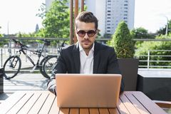 Male businessman or worker in black suit at the table and working on computer. Male businessman or worker with beard and sunglasses in black suit with shirt Royalty Free Stock Image