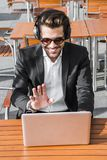 Male businessman or worker in black suit and headphones has conversation on computer. Male businessman or worker smiling in sunglasses, black suit with shirt in Royalty Free Stock Images