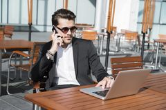 Male businessman or worker in black suit at the table and talking on phone. Male businessman or worker in black suit with shirt, bracelets and accessories on Royalty Free Stock Image
