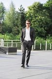 Male businessman or worker in black suit walk on the street stock images