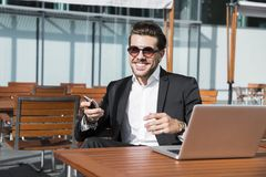 Male businessman or worker in black suit at the table with smartphone. Male businessman or worker in sunglasses and black suit with shirt and accessories on Stock Photos