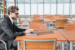 Male businessman or worker in black suit at the table and working on computer. Male businessman or worker with beard and sunglasses in black suit with shirt Stock Image