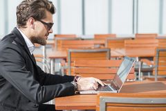 Male businessman or worker in black suit at the table and working on computer. Male businessman or worker with beard and sunglasses in black suit with shirt Stock Photo