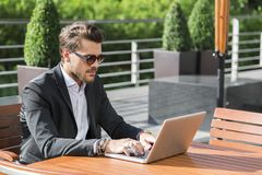 Male businessman or worker in black suit at the table and working on computer. Male businessman or worker with beard and sunglasses in black suit with shirt Royalty Free Stock Photos