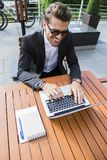 Male businessman or worker in black suit at the table and working on computer. Male businessman or worker in sunglasses and black suit with shirt and Royalty Free Stock Image