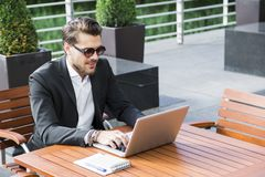 Male businessman or worker in black suit at the table and working on computer. Male businessman or worker in sunglasses and black suit with shirt and Stock Photo