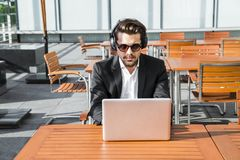 Male businessman or worker in black suit working on computer and listening to music. Male businessman or worker in sunglasses, black suit with shirt sitting Royalty Free Stock Photography