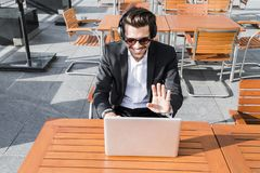 Male businessman or worker in black suit and headphones has conversation on computer. Male businessman or worker smiling in sunglasses, black suit with shirt in Royalty Free Stock Image
