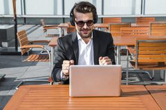 Male businessman or worker in black suit listening to music and dancing. Male businessman or worker smiling in sunglasses, black suit with shirt sitting in front Stock Images