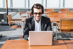 Male businessman or worker in black suit working on computer and listening to music. Male businessman or worker smiling in sunglasses, black suit with shirt Stock Photography