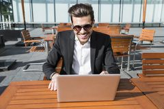 Male businessman or worker in black suit at the table and working on computer. Male businessman or worker in sunglasses and black suit with shirt and Royalty Free Stock Images