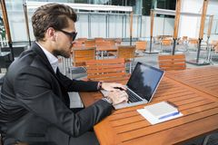 Male businessman or worker in black suit at the table and working on computer. Male businessman or worker in sunglasses, black suit with shirt and accessories Stock Photo