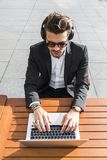 Male businessman or worker in black suit working on computer and listening to music. Male businessman or worker in sunglasses, black suit with shirt sitting Royalty Free Stock Image
