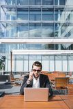 Male businessman or worker in black suit at the table and talking on phone. Male businessman or worker in sunglasses in black suit with shirt sitting outside at Stock Photography